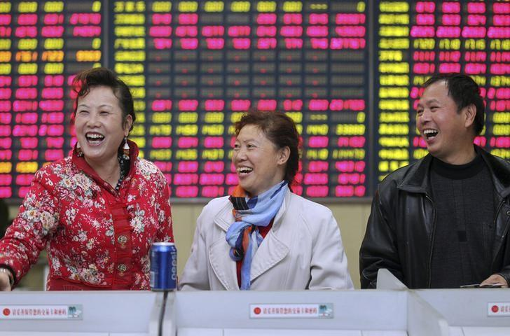 Investors laugh in front of an electronic screen showing stock information at a brokerage house in Nantong, Jiangsu province, November 24, 2014. Chinese stocks rose, with a key index hitting a three-year high, while bond yields fell on Monday. REUTERS/China Daily