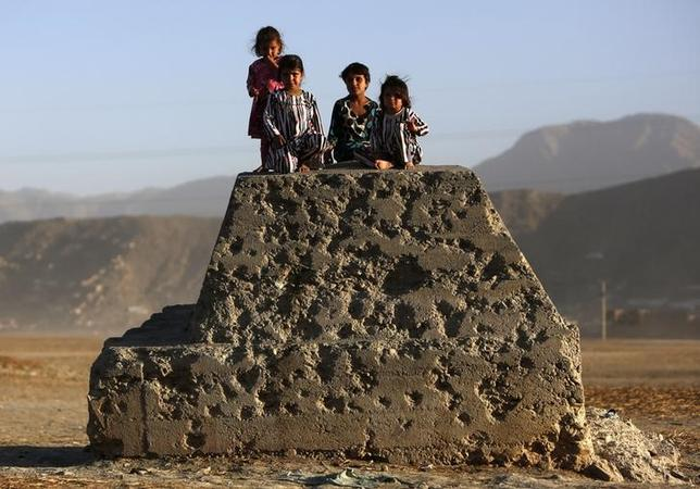 Afghan children sit on a bullet-riddled concrete block in Kabul October 21, 2013. REUTERS/Mohammad Ismail/Files
