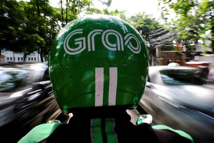 A Grab motor driver is seen in a street in Jakarta, Indonesia, February 13, 2017. REUTERS/Beawiharta/Files