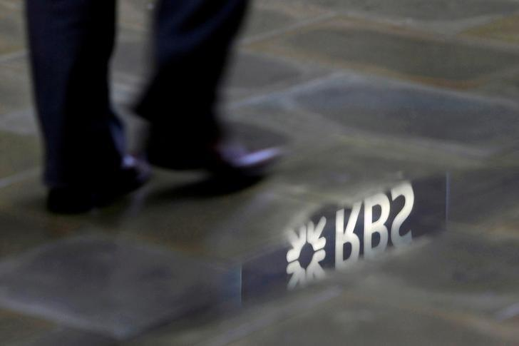 A man walks past a Royal Bank of Scotland branch logo reflected in a puddle in London, Britain, January 14, 2010.   REUTERS/Stefan Wermuth/File Photo/Files
