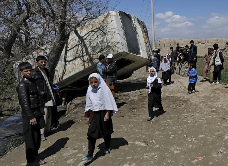 Schoolgirls walk past a damaged mini-bus after it was hit by a bomb blast in the Bagrami district of Kabul, Afghanistan April 11, 2016.  REUTERS/Mohammad Ismail