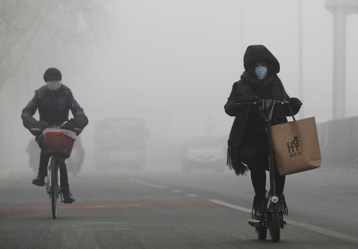 People ride amid the smog in Beijing, China, February 14, 2017. REUTERS/Jason Lee/Files