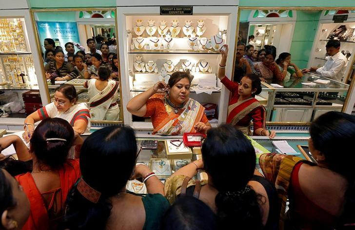 FILE PHOTO: A saleswoman displays a gold earring to customers at a jewellery showroom during Dhanteras, a Hindu festival associated with Lakshmi, the goddess of wealth, in Kolkata, India October 28, 2016. REUTERS/Rupak De Chowdhuri/File Photo