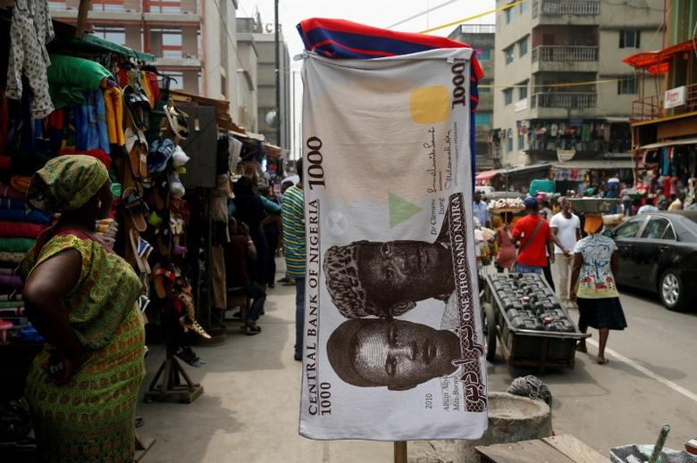 FILE PHOTO: A towel with a print of the Nigerian naira is displayed for sale at a street market in the central business district in Nigeria's commercial capital Lagos February 4, 2016. REUTERS/Akintunde Akinleye/File Photo