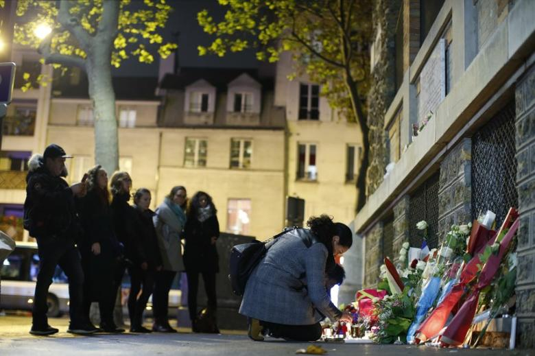 People pay their respects under a commemorative plaque next to the ''La Belle Equipe'' bar and restaurant in Paris, France, November 13, 2016, after a ceremony held for the victims of last year's Paris attacks which targeted the Bataclan concert hall as well as a series of bars and killed 130 people.      REUTERS/Gonzalo Fuentes