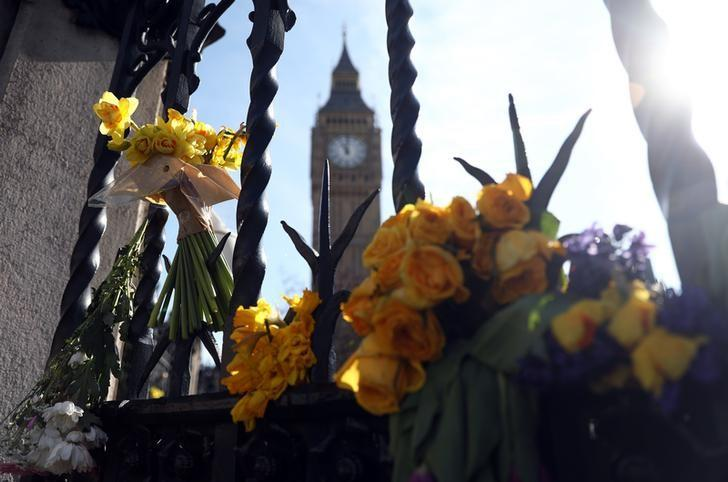 Floral tributes are tied to a fence in Parliament Square following the attack in Westminster earlier in the week, in central London, Britain March 26, 2017. REUTERS/Neil Hall