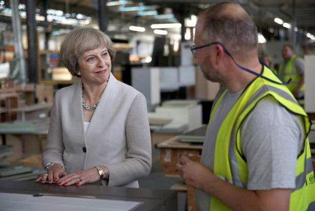 Britain's Prime Minister Theresa May (L) speaks with a worker as she visits a joinery factory in London, Britain August 3, 2016. REUTERS/Neil Hall
