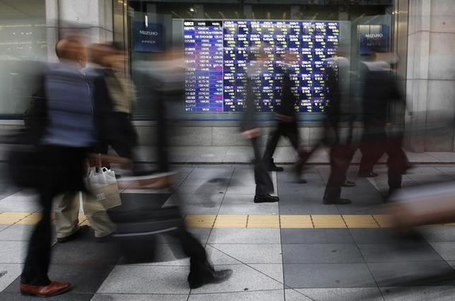 Passers-by walk past a stock quotation board outside a brokerage in Tokyo December 4, 2013. REUTERS/Toru Hanai/File Photo