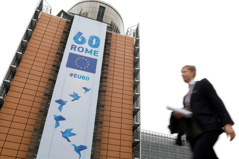 A man walks past the European Commission headquarters in Brussels on which is displayed a banner celebrating the 60 years after the signing of the Treaty of Rome, in Brussels, Belgium March 20, 2017.  REUTERS/Yves Herman