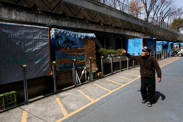 Homeless Makoto Shinbo walks past homeless people's makeshift houses as he takes a walk in Miyashita park in Tokyo, Japan, February 17, 2017. REUTERS/Kim Kyung-Hoon
