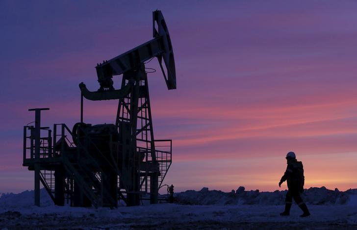 资料图片:2015年1月,俄罗斯Bashneft石油公司旗下油田的一名工人经过抽油机。REUTERS/Sergei Karpukhin