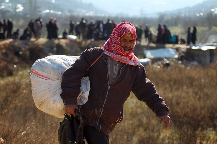 An internally displaced Syrian fleeing advancing pro-government Syrian forces carries his belongings near the Syrian-Turkish border after being given permission by the Turkish authorities to enter Turkey, in Khirbet Al-Joz, Latakia countryside February 2, 2016. REUTERS/Ammar Abdullah/Files