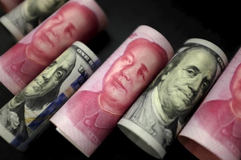资料图片:2016年1月,图为百元面值的人民币纸币和美元现钞。REUTERS/Jason Lee