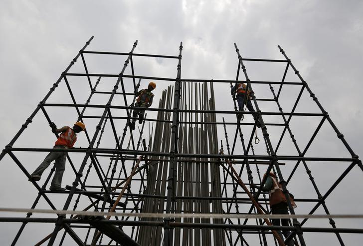 Workers erect scaffolding to build a pillar at the site of the metro railway flyover under construction in Ahmedabad, India, June 30, 2016. REUTERS/Amit Dave