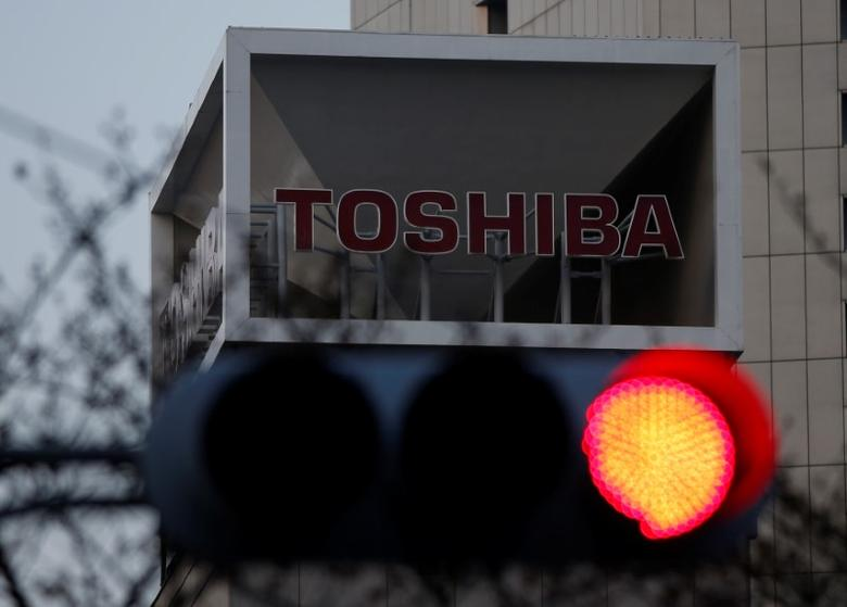 The logo of Toshiba Corp is seen behind a traffic light at the company's headquarters in Tokyo, Japan March 29, 2017. REUTERS/Issei Kato