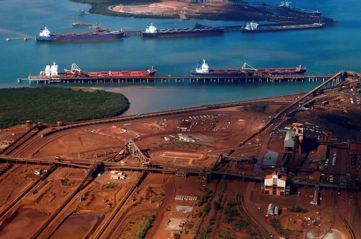 Ships waiting to be loaded are seen near piles of iron ore and bucket-wheel reclaimers at the Fortescue loading dock located at Port Hedland in the Pilbara region of Western Australia December 3, 2013.    REUTERS/David Gray/File Photo