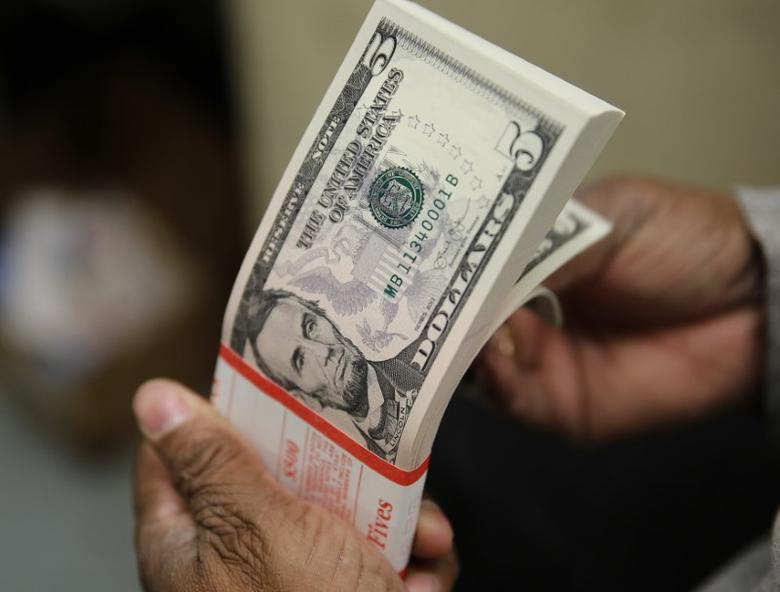 A packet  of former U.S. President Abraham Lincoln five-dollar bill currency is inspected at the Bureau of Engraving and Printing in Washington March 26, 2015. REUTERS/Gary Cameron/File Photo