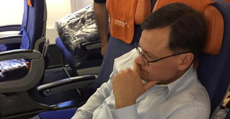 Evgeny Buryakov, a former New York banker who was convicted in federal court of conspiring to act in the United States as an agent of the Russian Federation, is shown in this handout photo sitting on a commercial flight, escorted by deportation officers and turned over to Russian authorities, April 5, 2017.    United States Immigration and Customs Enforcement (ICE)/Handout via REUTERS