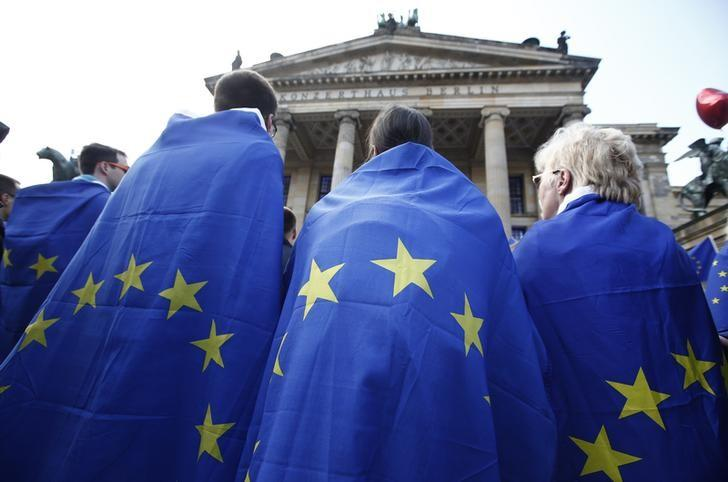 People are wrapped in European Union flags as they attend the Pro-Europe ''Pluse of Europe'' movement protest at Gendarmenmarkt square in Berlin, Germany, April 2, 2017. REUTERS/Fabrizio Bensch