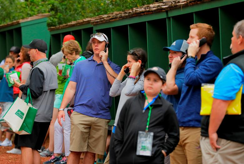 Patrons use landline phones to call out as cell phones are not allowed on the course during Monday practice rounds for the 2017 Masters at Augusta National Golf Course in Augusta, Georgia, U.S., April 3, 2017. REUTERS/Jonathan Ernst