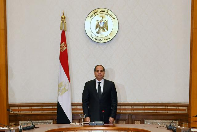Egyptian President Abdel Fattah al-Sisi stands and observes a minute of silence for the victims of two separate church attacks during Palm Sunday prayers, with leaders of the Supreme Council of the Armed Forces and the Supreme Council for Police to discuss developments in the security situation in Egypt, as well as developments in the country's fight against terrorism, at the Ittihadiya presidential palace in Cairo, Egypt, April 9, 2017, in this handout picture courtesy of the Egyptian Presidency. The Egyptian Presidency/Handout via REUTERS