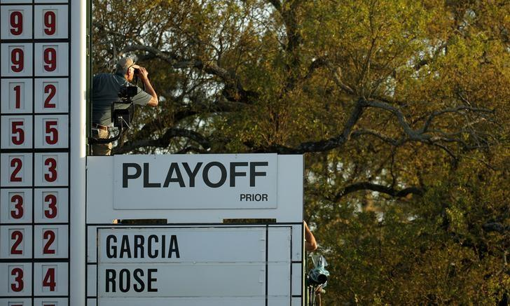 A scoreboard operator uses binoculars by a playoff sign on the 18th green after regulation play ended in a tie between Justin Rose of England and Sergio Garcia of Spain at the 2017 Masters golf tournament at Augusta National Golf Club in Augusta, Georgia, U.S., April 9, 2017. REUTERS/Brian Snyder