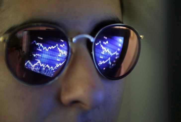 A computer screen showing stock graphs is reflected on glasses in this illustration photo taken in Bordeaux, France, March 30, 2016. REUTERS/Regis Duvignau/Files