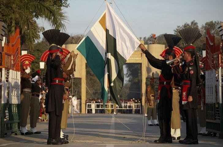 Pakistan Rangers (R) and Indian Border Security Force personnel take part in the daily flag lowering ceremony at their joint border post of Wagah near Lahore February 10, 2011. REUTERS/Mohsin Raza/File Photo