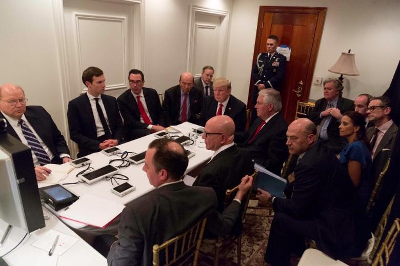 U.S. President Donald Trump is shown in an official White House handout image meeting with his National  Security team and being briefed by Chairman of the Joint Chiefs of Staff General Joseph Dunford via secure video teleconference after a missile strike on Syria while inside the Sensitive Compartmented Information Facility at his Mar-a-Lago resort in West Palm Beach, Florida, U.S. April 6, 2017. White House Press Secretary Sean Spicer stated that this image has been digitally edited for security purposes when he released the photo via Twitter on April 7, 2017.  The White House/Handout via REUTERS