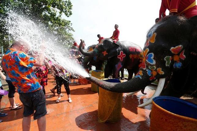 4月11日、タイのアユタヤで、旧暦の新年を祝う恒例の「水かけ」が早くも始まった。照りつける太陽の下、カラフルな模様をペイントされたゾウたちが、世界中から訪れた観光客に水をかけ、盛り上がった(2017年 ロイター/Chaiwat Subprasom )