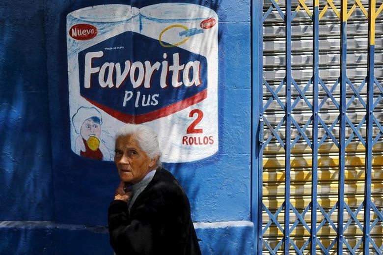 A woman walks past an advertisement of a tissue paper brand of Swedish SCA company on a street in Santiago, Chile, November 10, 2015. REUTERS/Ivan Alvarado
