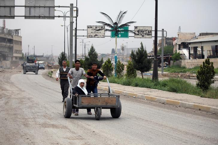Two boys push a wheelbarrow carrying an elder woman along a street in an area controlled by Iraqi forces fighting the Islamic State in western Mosul, Iraq, April 13, 2017. REUTERS/Andres Martinez Casares
