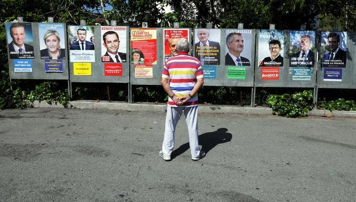 2017年4月10日,法国Saint Andre de La Roche,一名男子观看总统候选人海报。REUTERS/Eric Gaillard