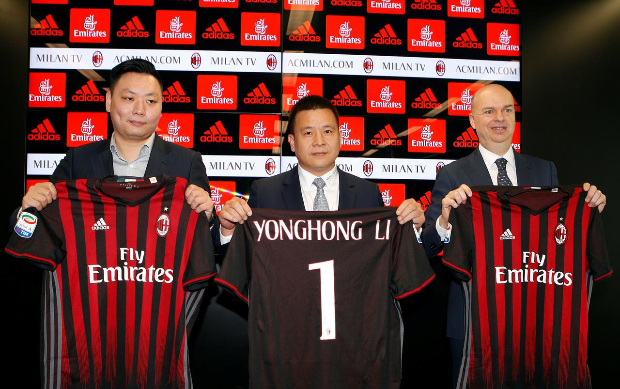 New chinese owners of italys ac milan football club to invest in david han li l yonghong li c and marco fassone show a ac milan jersey during a news conference in milan italy april 14 2017 voltagebd Image collections