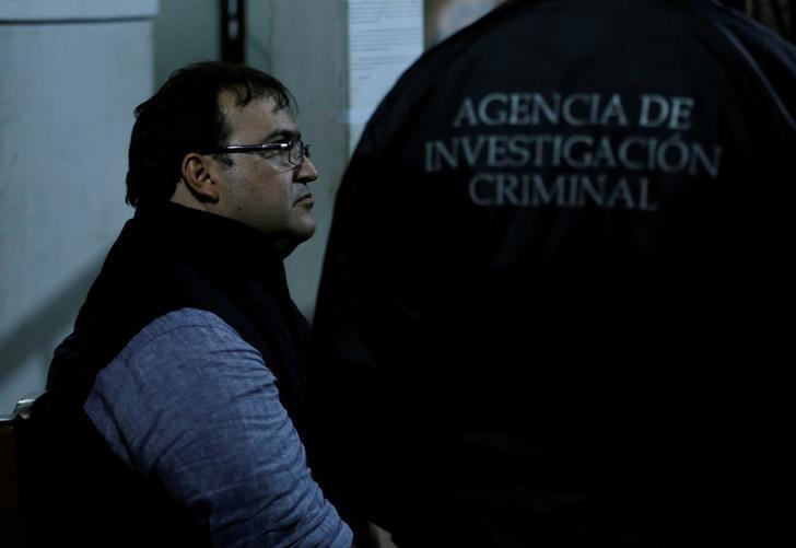 Former governor of Mexican state Veracruz Javier Duarte (L) sits at a police station after he was detained in a hotel in Panajachel, Guatemala April 15, 2017. The writing on the jacket reads ''Criminal investigation agency''.  REUTERS/Danilo Ramirez