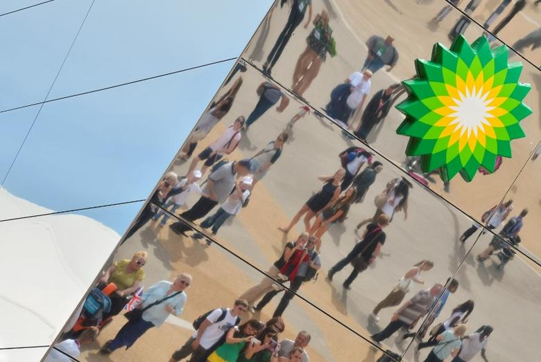 Spectators are seen reflected in a British Petroleum sponsors building in Olympic Park at the London 2012 Paralympic Games September 6, 2012. REUTERS/Toby Melville/File Photo
