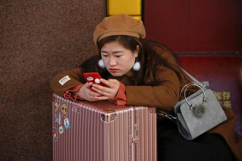 A passenger checks her phone at a waiting hall of the Beijing Railway Station in central Beijing, China January 27, 2017 as China gears up for Lunar New Year, when hundreds of millions of people head home.    REUTERS/Damir Sagolj - RTSXKZ9