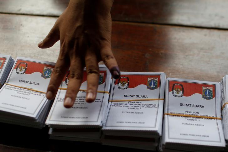 An election official counts ballots during the counting process after polls closed in the governor election in Jakarta, Indonesia April 19, 2017. REUTERS/Beawiharta
