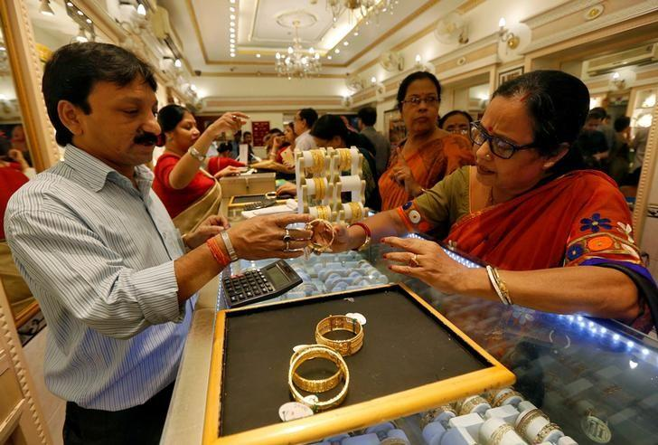 FILE PHOTO: A salesman shows gold bangles to a customer at a jewellery showroom during Dhanteras, a Hindu festival associated with Lakshmi, the goddess of wealth, in Kolkata, India October 28, 2016. REUTERS/Rupak De Chowdhuri/File Photo