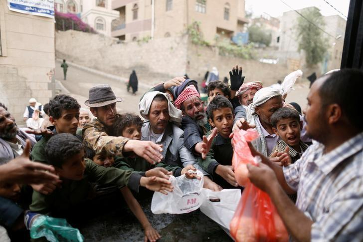 People gather to collect food rations at a food distribution center in Sanaa, Yemen March 21, 2017. REUTERS/Khaled Abdullah