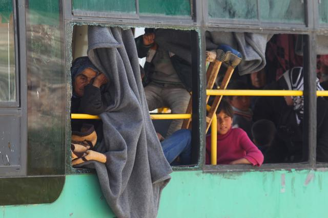 People, who were evacuated from the two rebel-besieged Shi'ite villages of al-Foua and Kefraya, ride a bus in insurgent-held al-Rashideen, to travel to government-controlled Aleppo, Syria April 21, 2017. REUTERS/Ammar Abdullah