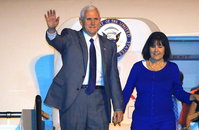 U.S. Vice President Mike Pence waves as he exits his plane with wife Karen after arriving at Sydney International Airport in Australia, April 21, 2017.      REUTERS/Jason Reed