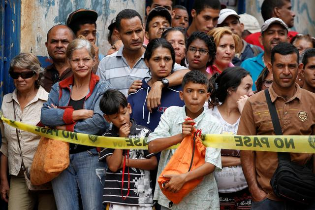 People look at police officers and criminal investigators while they collect evidence in front of a bakery, after it was looted in Caracas, Venezuela April 21, 2017. REUTERS/Carlos Garcia Rawlins