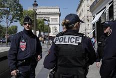 أفراد من الشرطة الفرنسية يحرسون في جادة الشانزيليزيه يوم الجمعة. توصير: بينواه تيسيه - رويترز