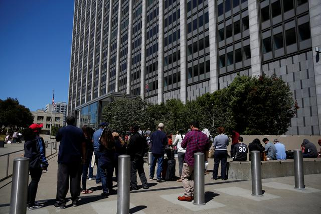 People wait outside the Phillip Burton Federal Building & United States Courthouse during a major power outage in San Francisco, California, U.S., April 21, 2017. REUTERS/Stephen Lam