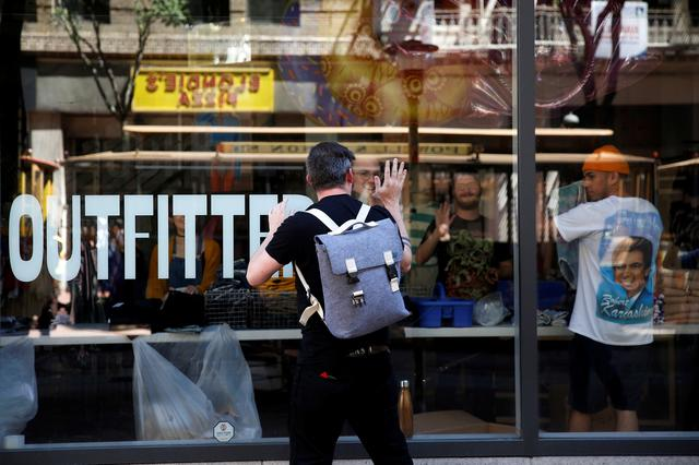A man gestures to workers inside a darkened Urban Outfitters during a major power outage in San Francisco, California, U.S., April 21, 2017. REUTERS/Stephen Lam