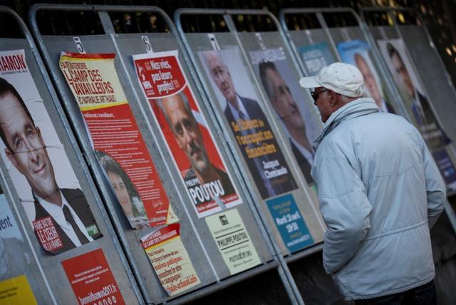 4月20日、昨年の米大統領選ほどではないものの、23日に最初の投票が行われるフランス大統領選においても、ソーシャルメディアに出回る大量の「偽ニュース」に有権者がさらされていることが明らかになった。写真は仏大統領候補のポスターを眺める男性。パリ近郊で19日撮影(2017年 ロイター/Christian Hartmann)