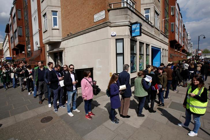 French expats queue along the street and around the block outside the Lycee Francais Charles de Gaulle to cast their vote in a polling station inside the school, in the first round of the 2017 French presidential election, in London, Britain April 23, 2017.  REUTERS/Luke MacGregor