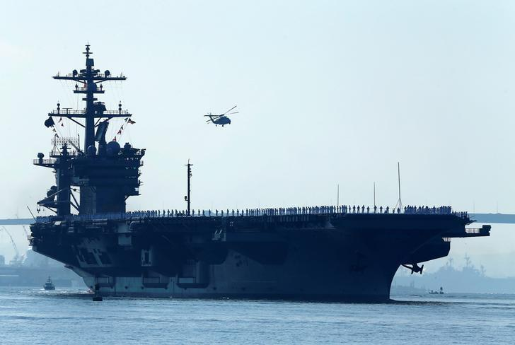 FILE PHOTO - Sailors man the rails of the USS Carl Vinson, a Nimitz-class aircraft carrier, as it departs its home port in San Diego, California August 22, 2014. REUTERS/Mike Blake/File Photo