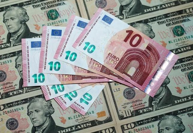 4月24日、終盤のニューヨーク外為市場では、ユーロがドルと円に対して急伸。写真はユーロとドルの紙幣、2015年3月撮影(2017年 ロイター/Heinz-Peter Bader)